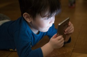 child staring at phone screen