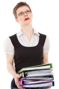Stressed woman holding large stack of paperwork