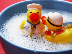 2 rubber ducks in soapy water