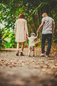 Mom and dad walking on outdoor path holding child's hands between them