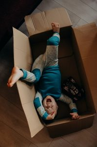 Child playing in cardboard box