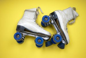 white roller skates with blue wheels on yellow background